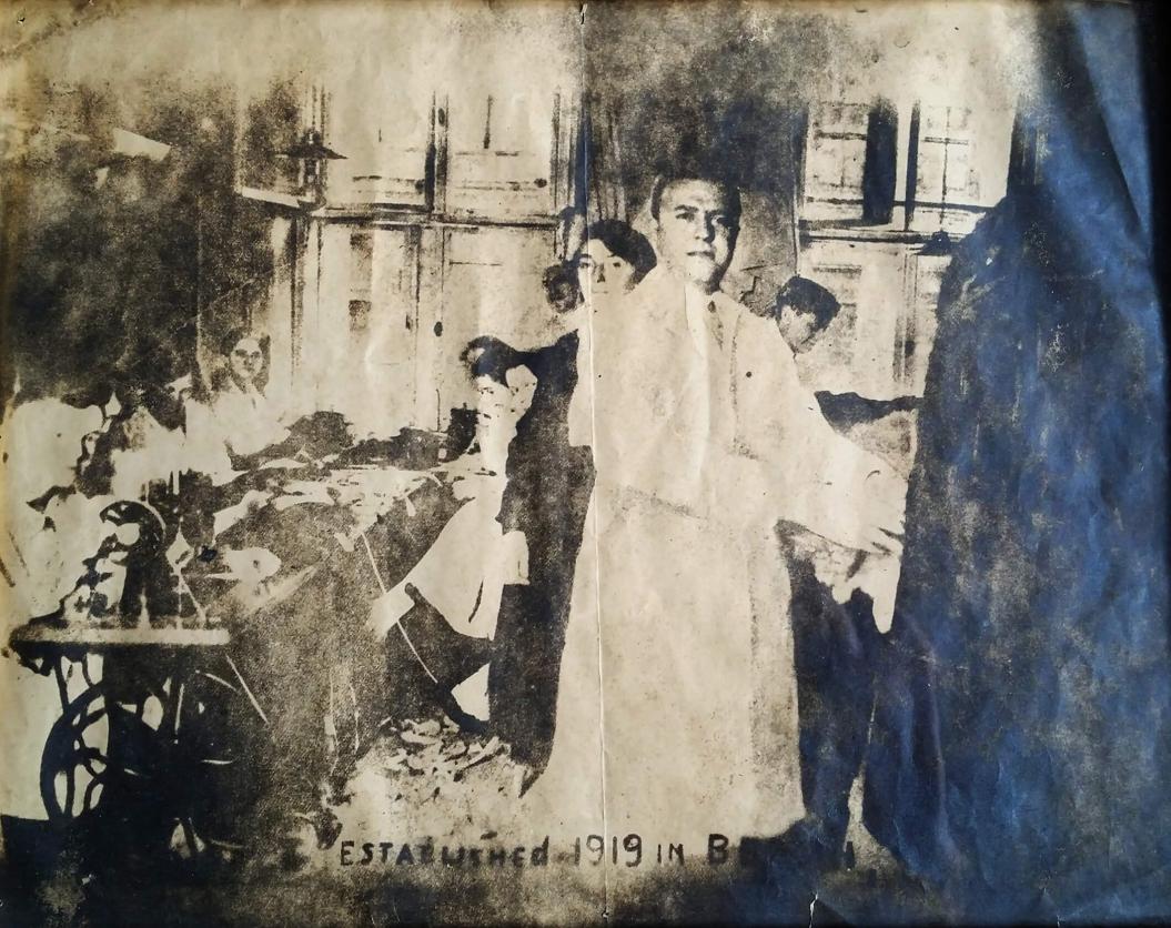 schwarz-weiß-Foto: Mann im weißen Kittel, neben einem Pelz stehend, dahinter mehrere Personen, nur schemenhaft zu erkennen