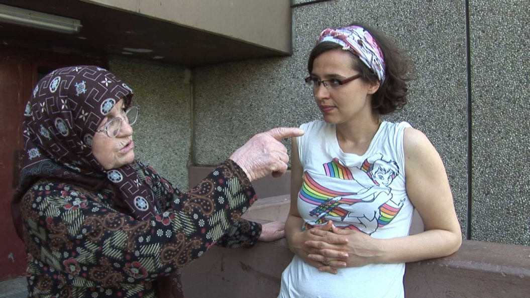 An older woman with glasses and headscarf (left in the picture) is talking to a younger woman who also wears glasses and is standing at the right edge of the picture.