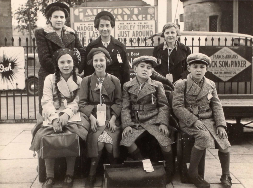Black-and-white group photo of seven children in coats with baggage.