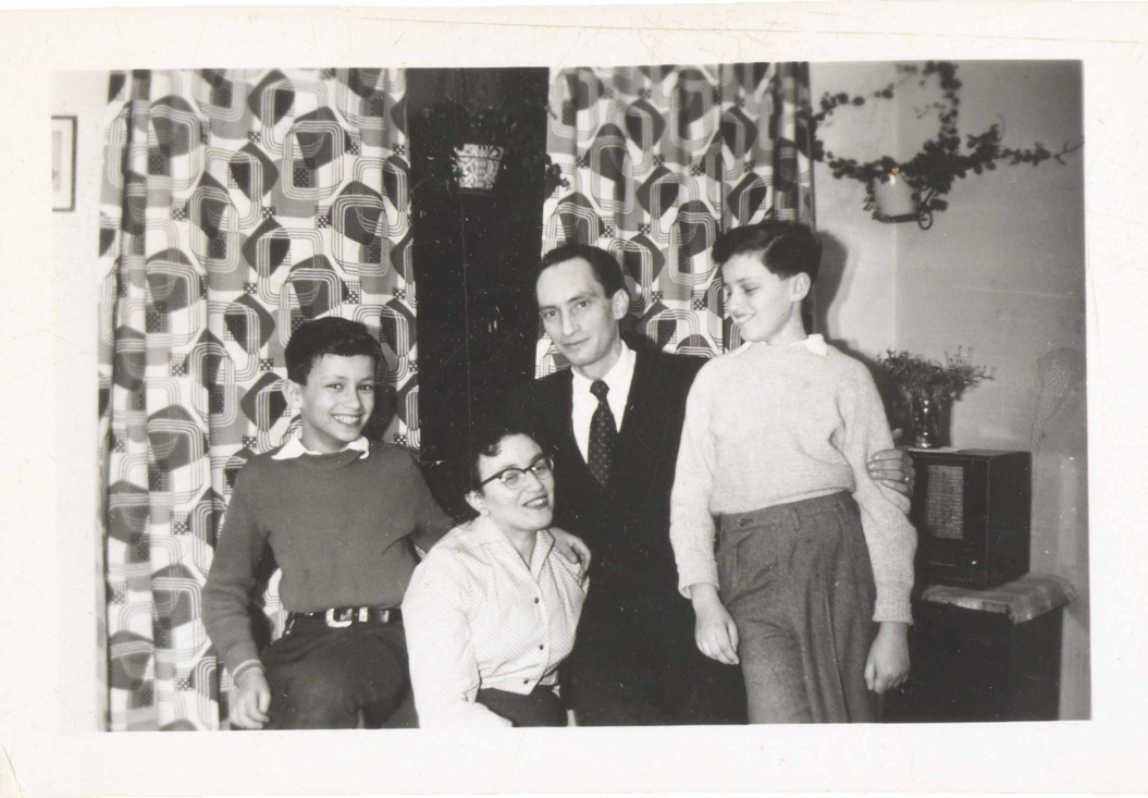 In the black-and-white photo, the family is in a room with patterned curtains and houseplants. All four are smiling or laughing. The image is very lively.