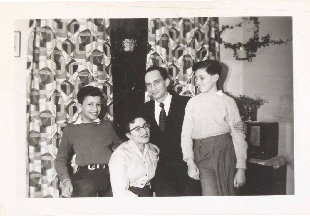 Auf dem Schwarz-Weiß-Foto steht die Familie vor gemusterten Vorhängen und Zimmerpflanzen. Alle vier lachen oder lächeln. Das Bild wirkt bewegt.