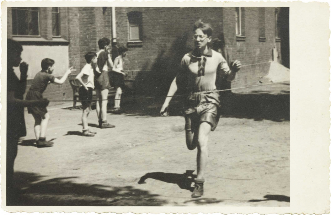 In the foreground of the picture you can see a running boy, who is about to reach the finish line, boys watching in the background (black and white photo)