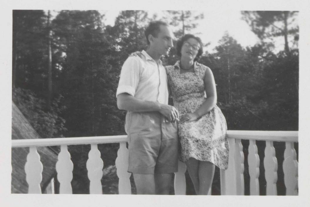 Auf dem Schwarz-Weiß-Foto sitzt Leonie im Sommerkleid auf der Balkonbrüstung. Walter steht neben ihr, hat den linken Arm um sie gelegt und hält in der rechten Hand eine Zigarette.