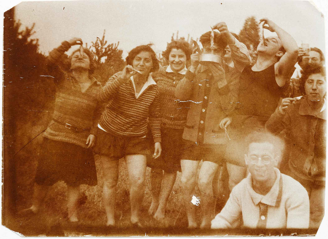 Gruppenbild von acht Frauen und Männern mit kurzen Hosen oder Röcken im Freien, die kleine Fische zum Mund führen