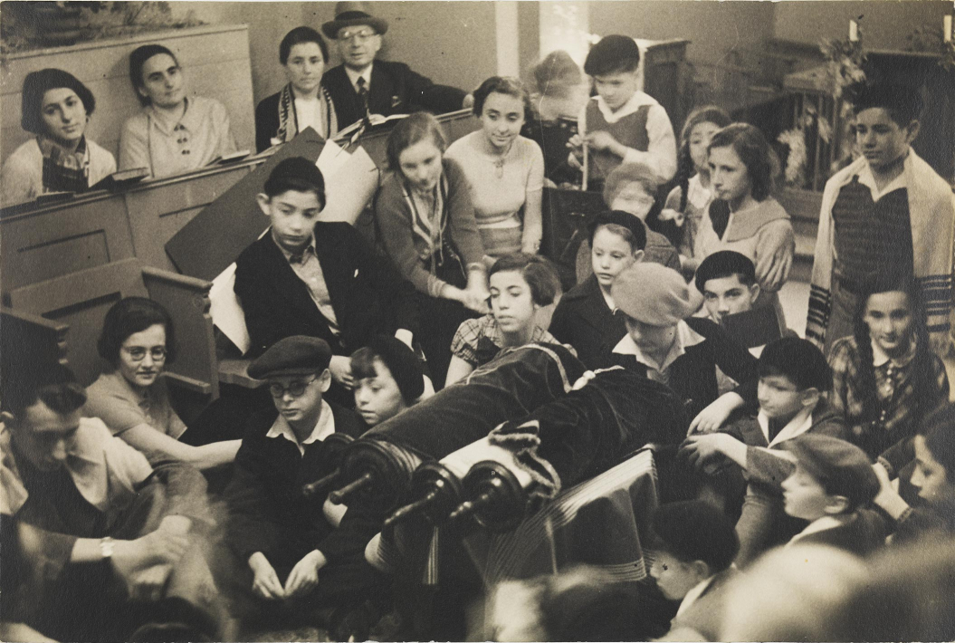 Black-and-white photograph showing children and teenagers at a festive prayer service in a synagogue