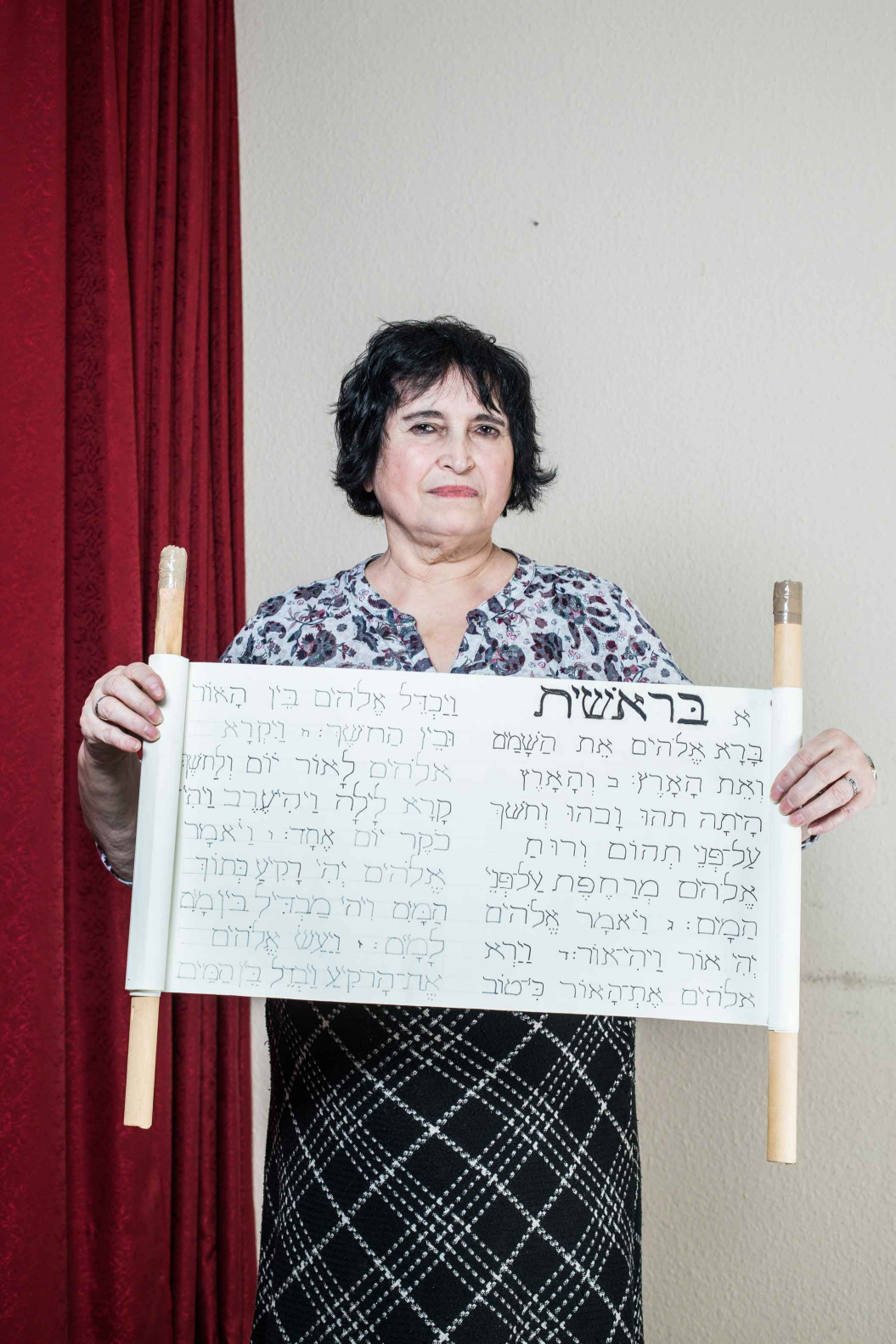 A woman holding a Torah scroll in her hands