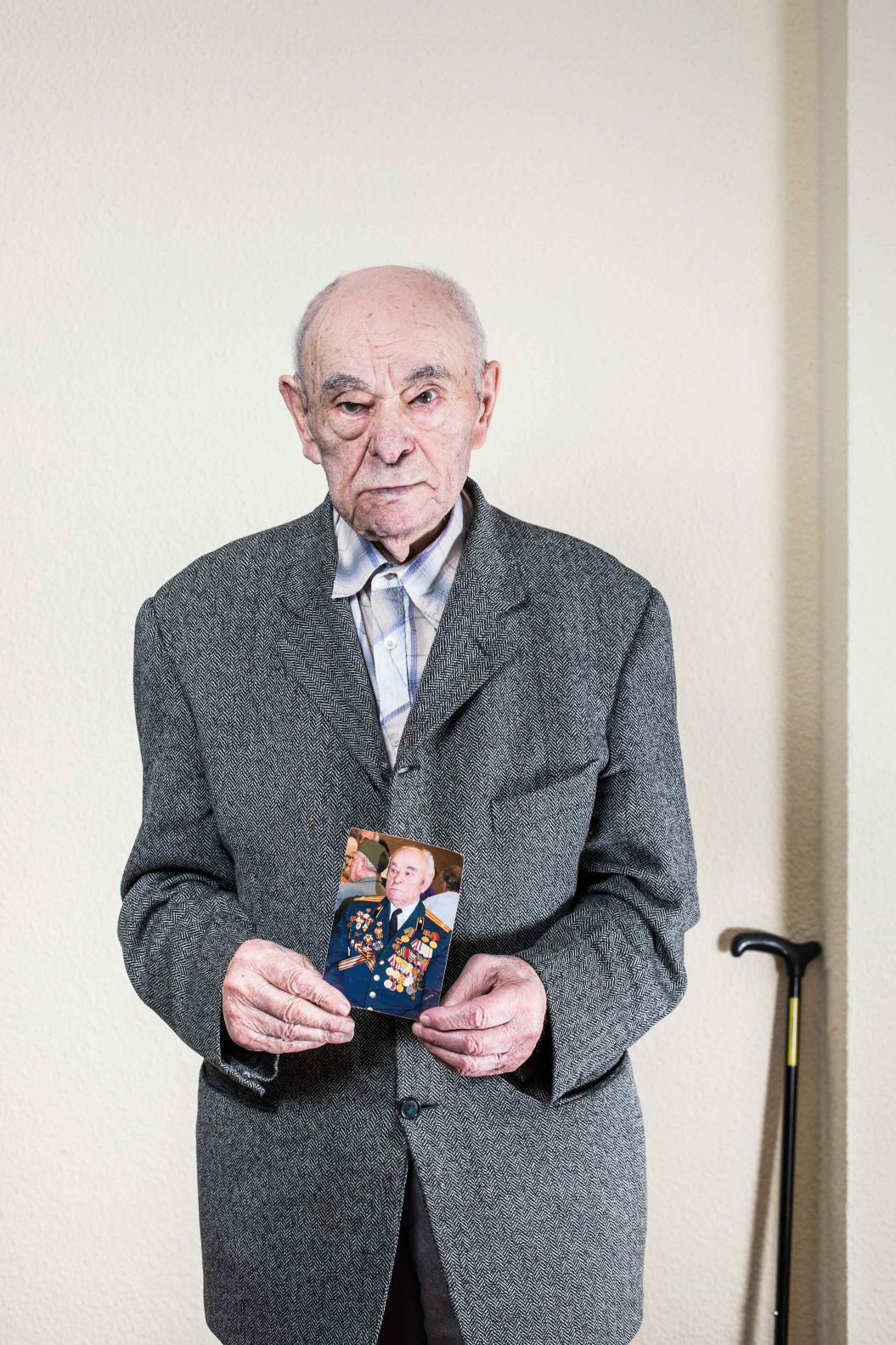 elderly man in grey suit holding a photo of himself covered in medals and decorations