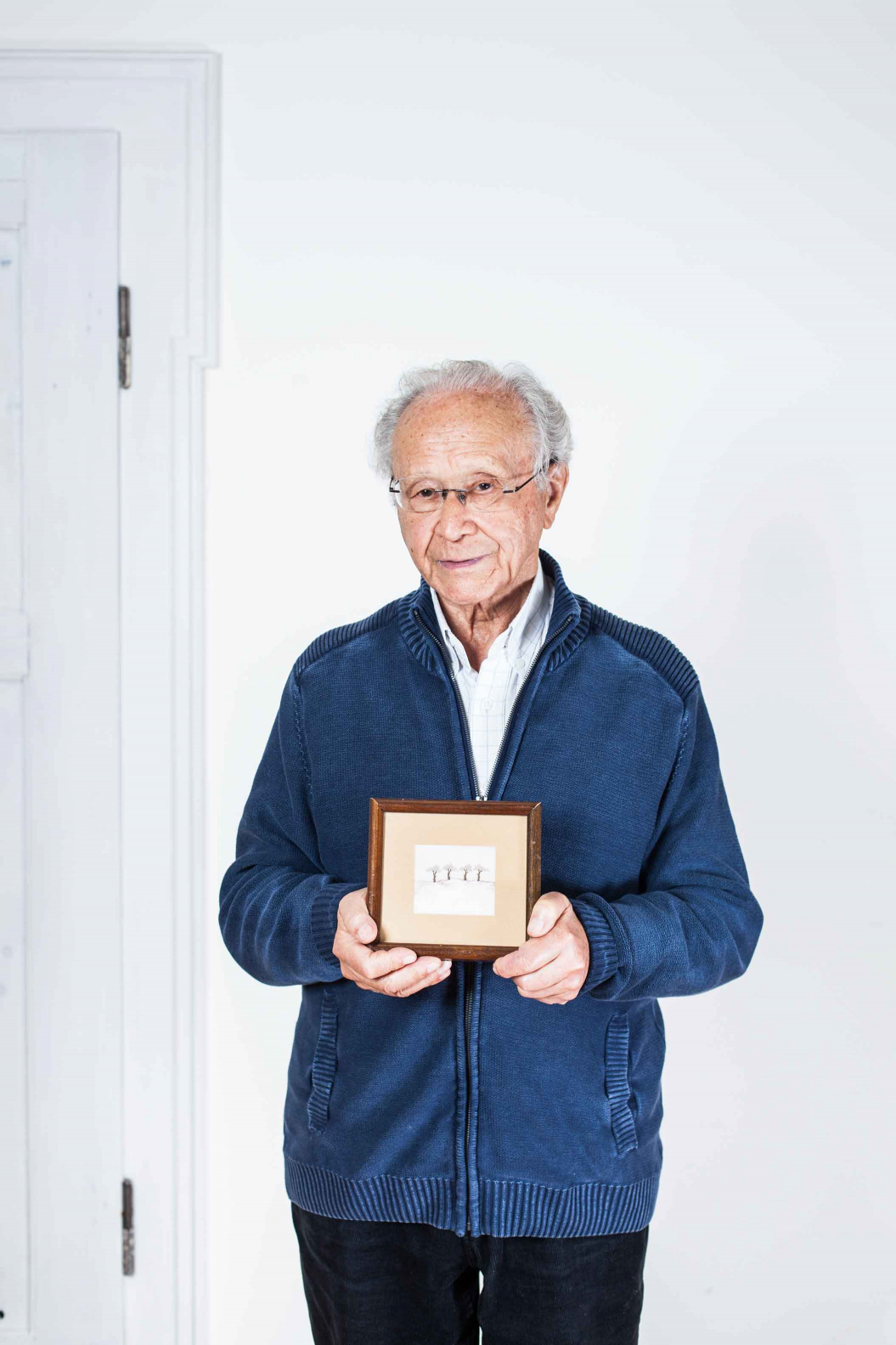 Elderly man holding a drawn picture with four trees in a frame in his hands