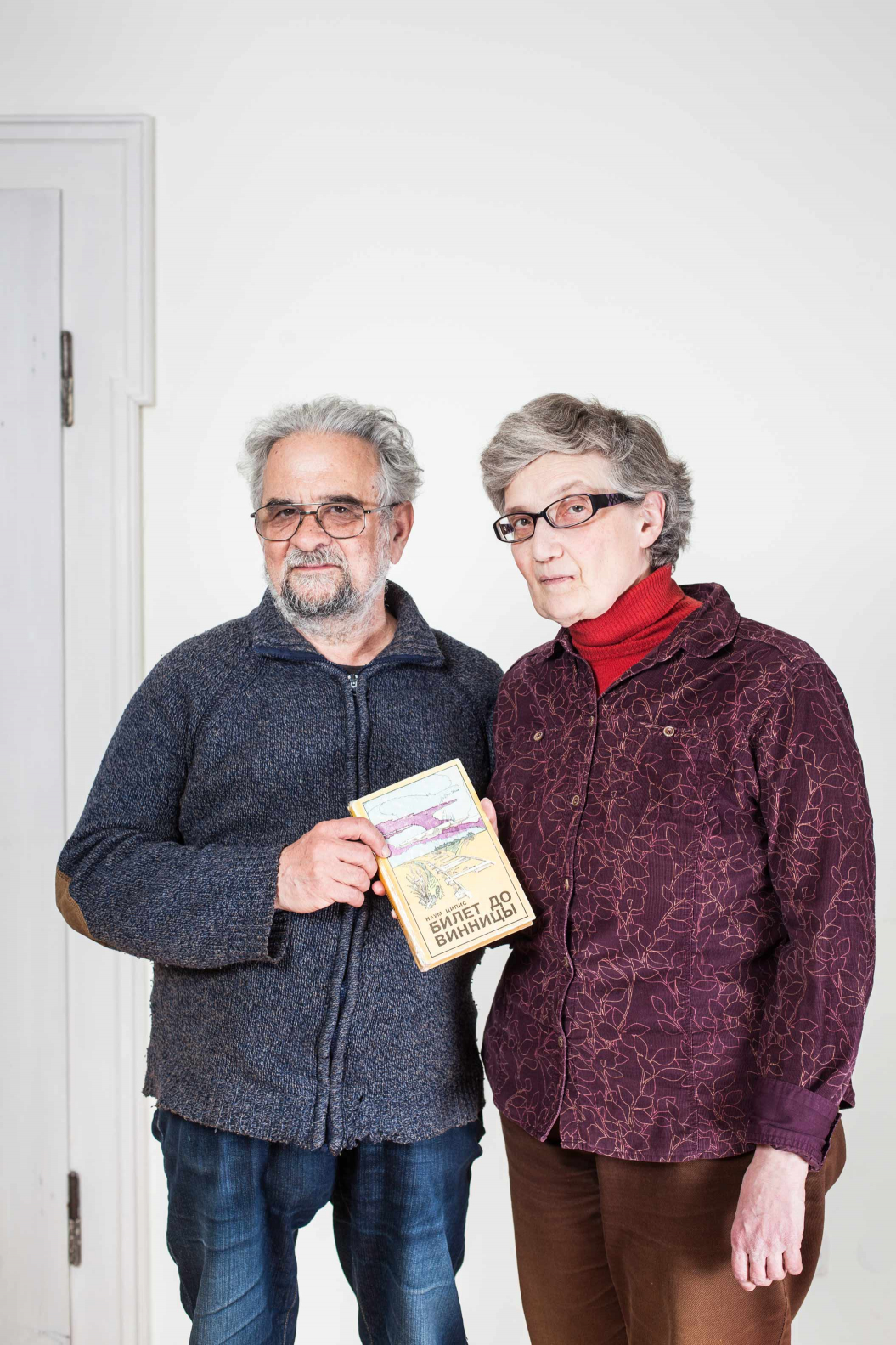 Elderly man and elderly lady holding a book together