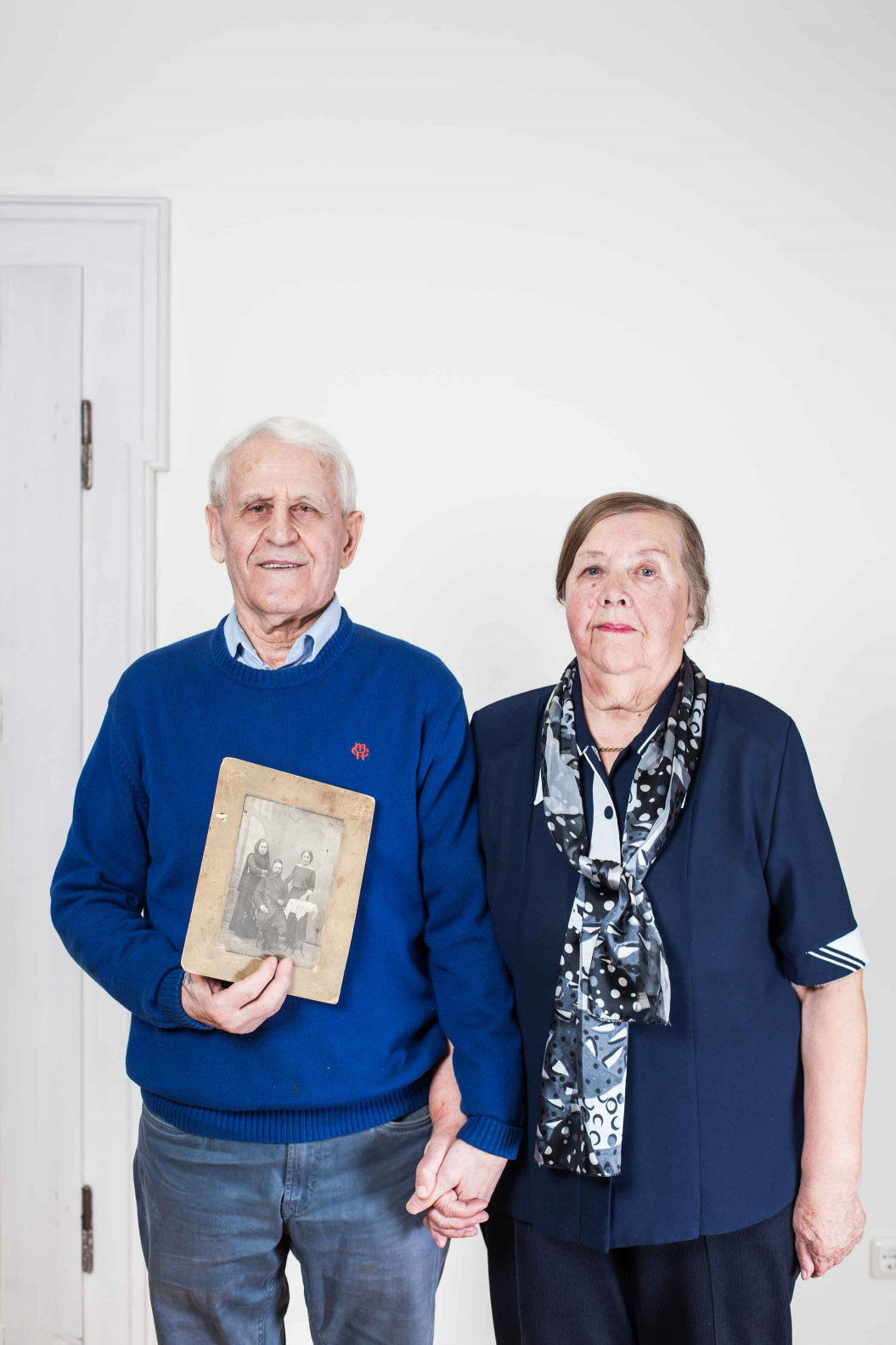 An elderly couple holding an old black and white photograph in their hands