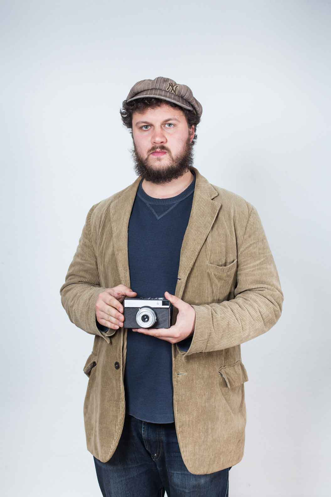 A young man with a cap and beard in a brown corduroy jacket is holding an analogue camera in his hands.