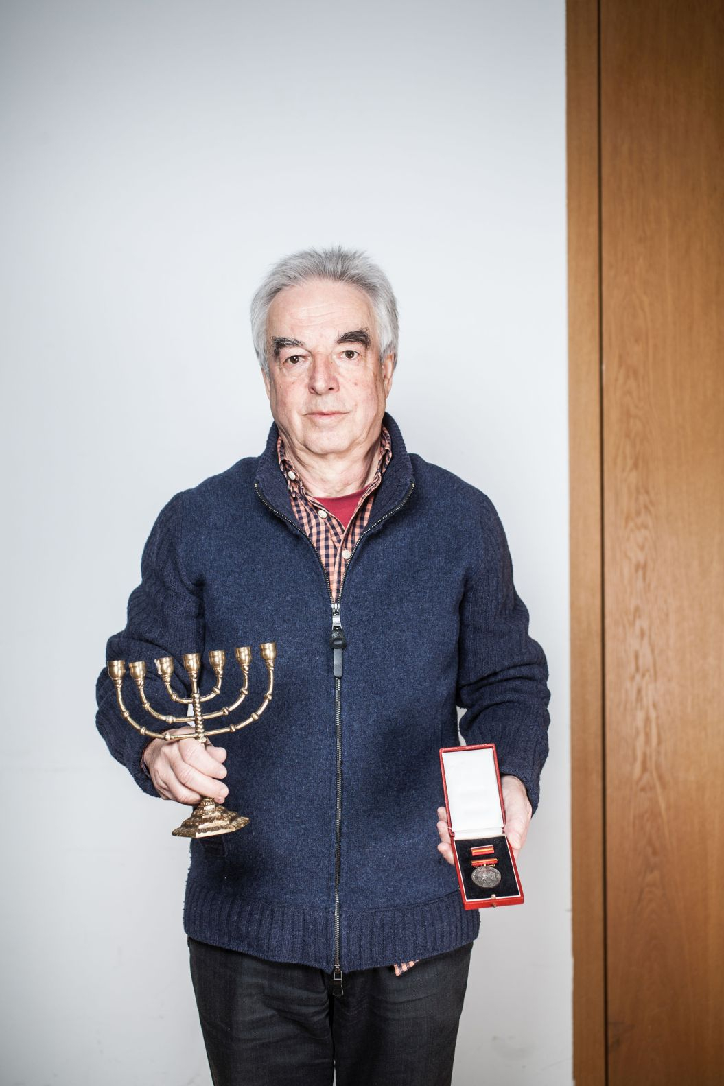 A gray-haired man holds a menorah in one hand and a medal in the other.