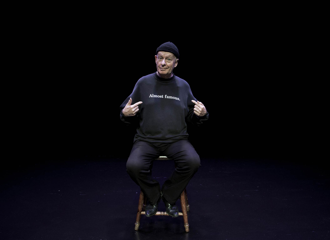 Man sitting on a stool, dark background