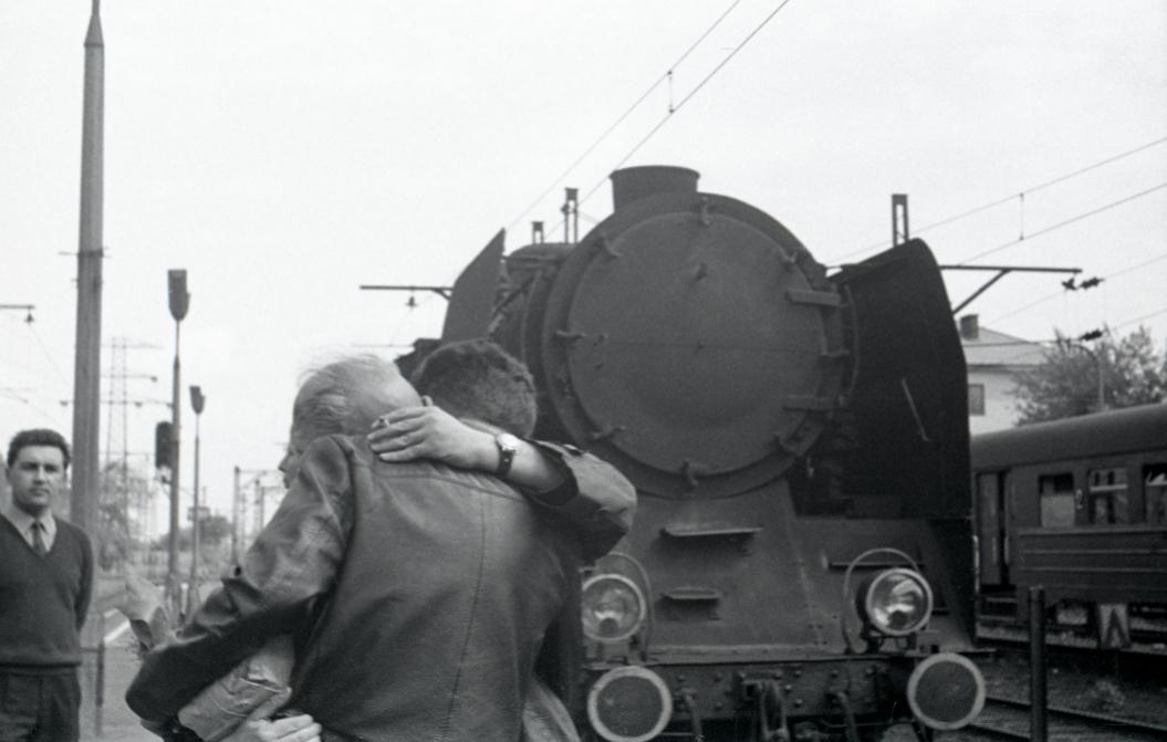 Zwei Männer umarmen sich auf einem Bahnhof