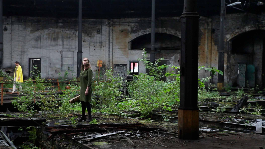 A woman stands in the middle of an old decaying building and looks up, she is surrounded by plants and remains of the building