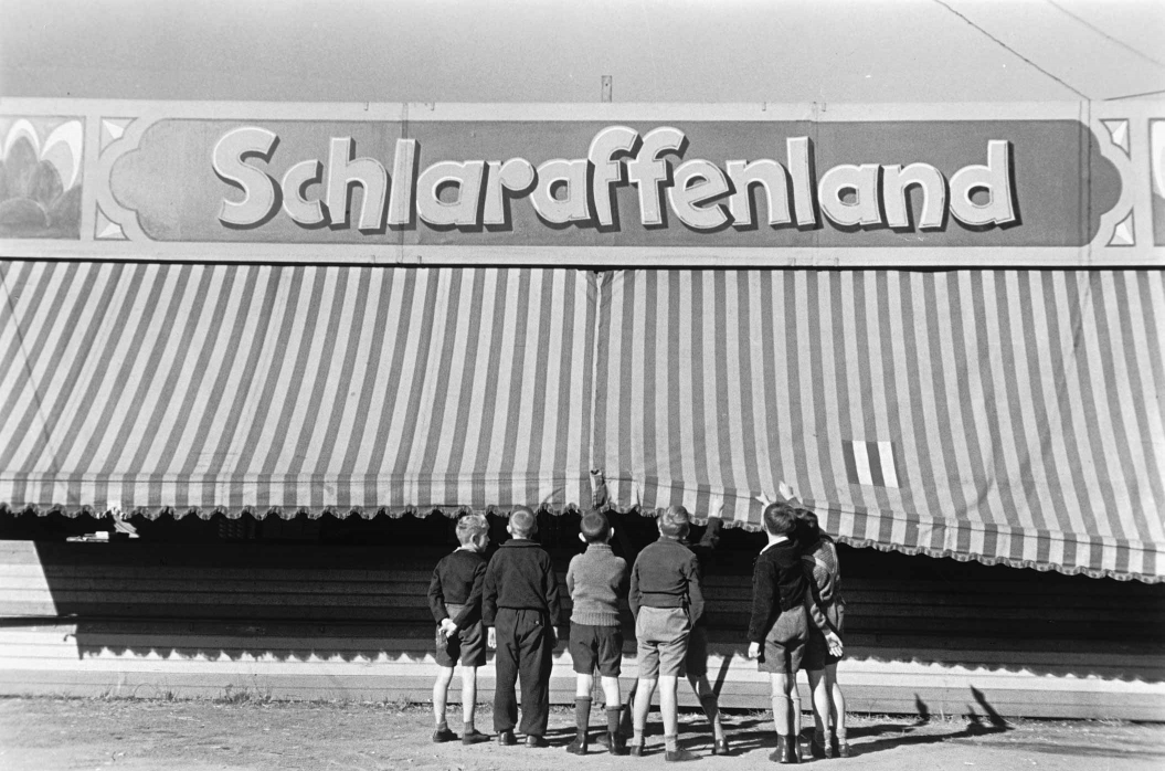 "Historical photograph of a group of children standing in front of a large tent called ""Schlaraffenland"""