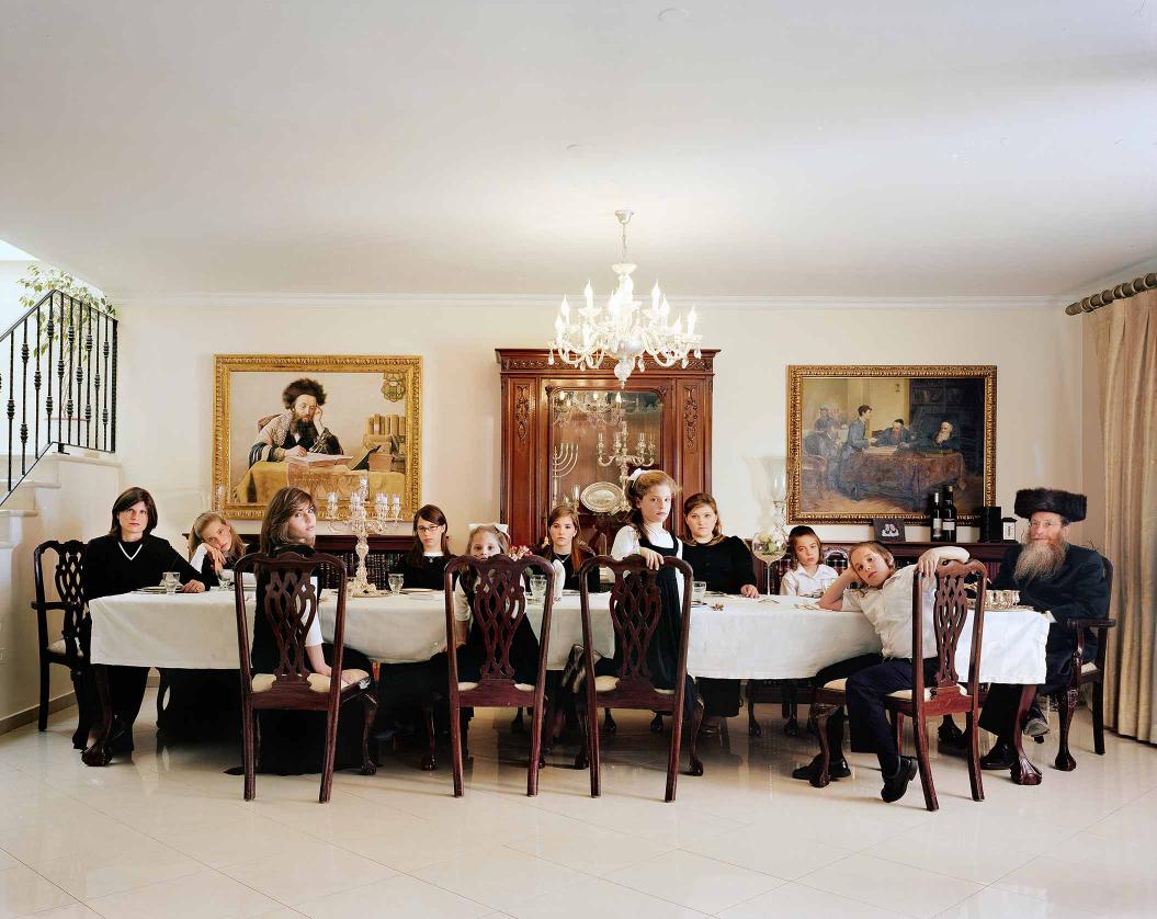 Foto zweier Erwachsener und neun Kinder um einen großen Esstisch in repräsentativem Wohnraum mit Kronleuchter und Gemälden an der Wand