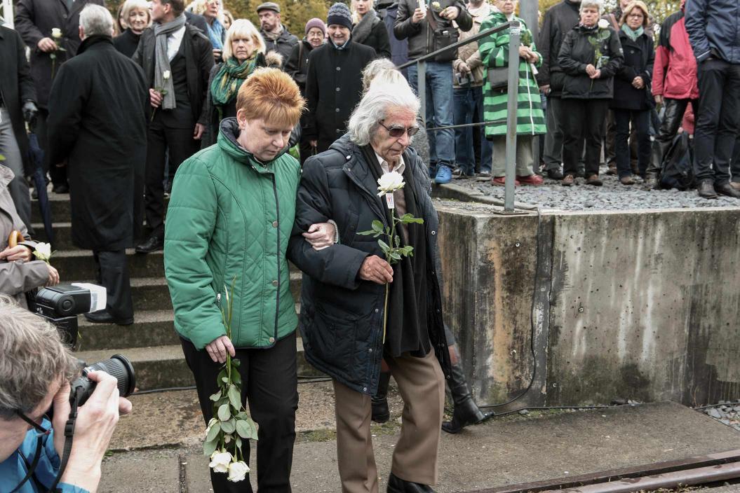 Horst Selbiger mit Petra Pau bei einer Gedenkveranstaltung, in der Hand eine weiße Rose