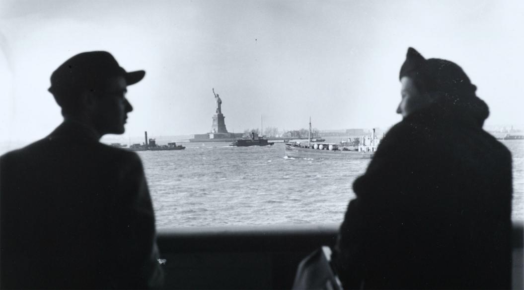 Ein Mann und eine Frau sich anschauend, im Halbprofil, auf einem Schiff, zwischen ihnen ist der Blick übers Wasser frei auf die Freiheitsstatue