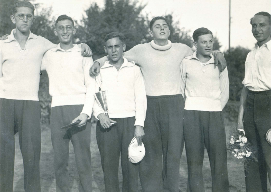Black-and-white photograph of a rowing team holding a trophy