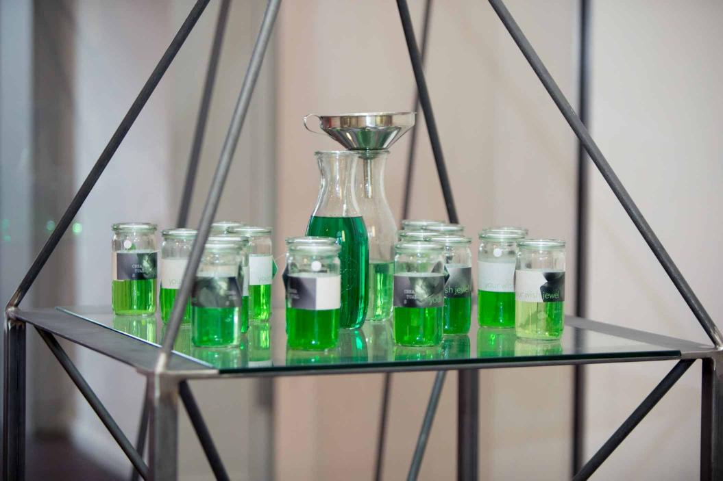 Mehrere mit grüner Flüssigkeit gefüllte Gläser und zwei Krüge, einer davon mit einem Trichter