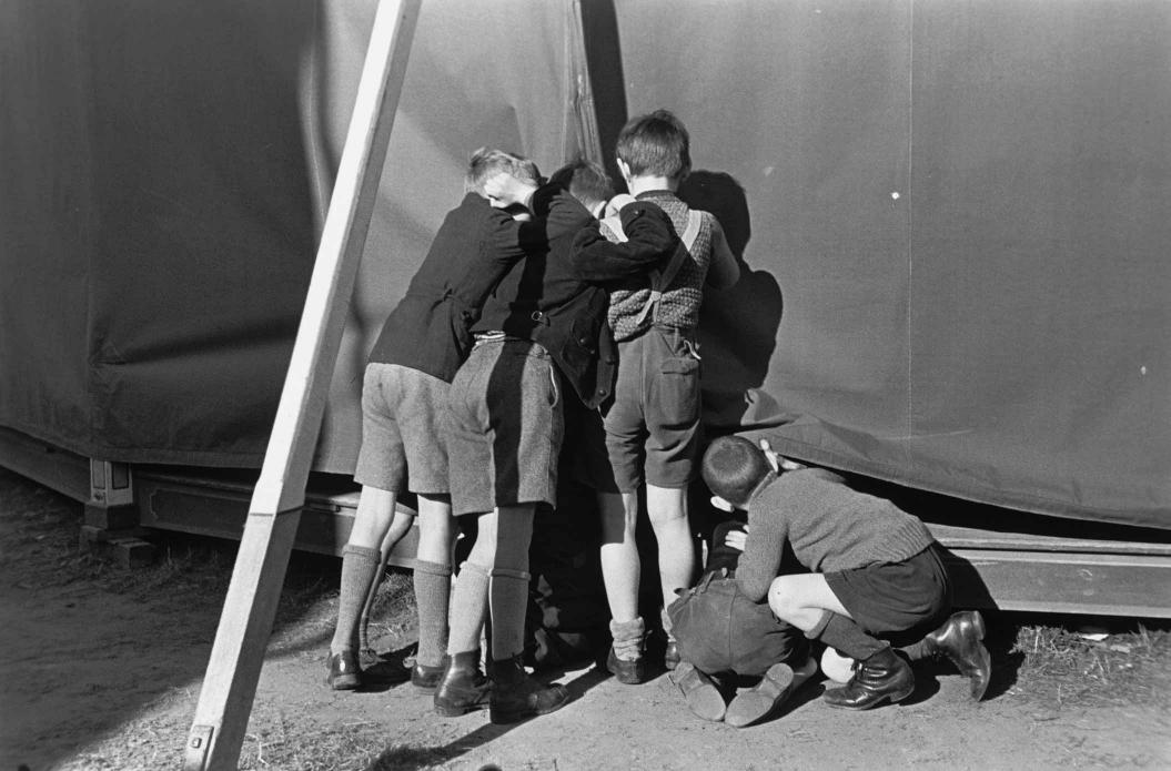 Vier Jungs sehen auf dem Jahrmarkt heimlich in ein Zelt hinein, Schwarz-Weiß-Foto