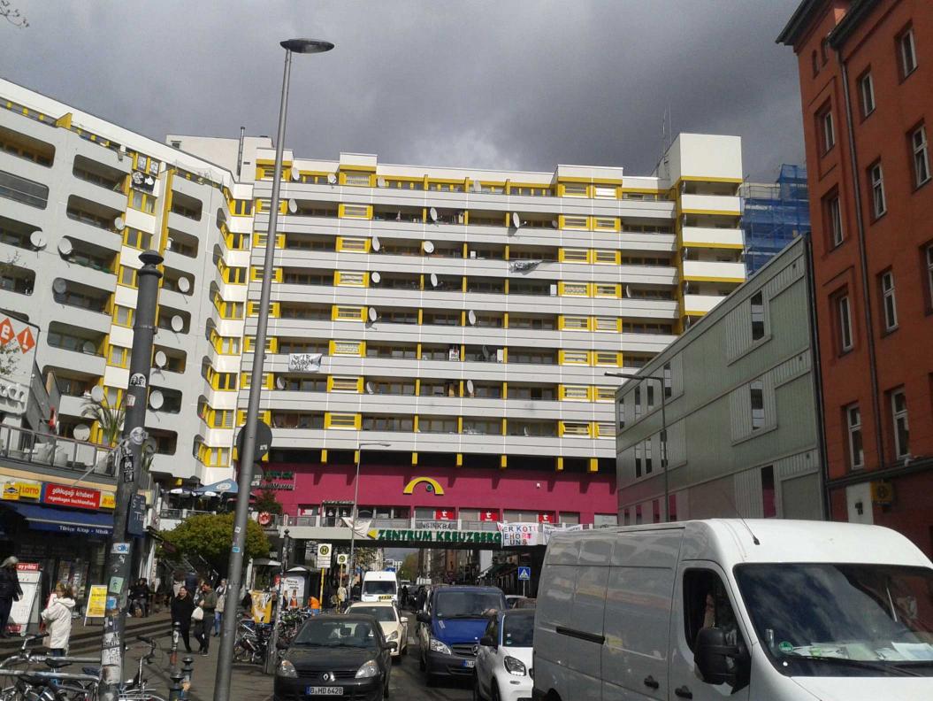 Fotografie eines Gebäuderiegels über einer autobefahrenen Straße