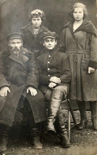 Black-and-white group photo: a man with a beard and a boy, seated, with a younger and older girl standing behind them, all wearing overcoats