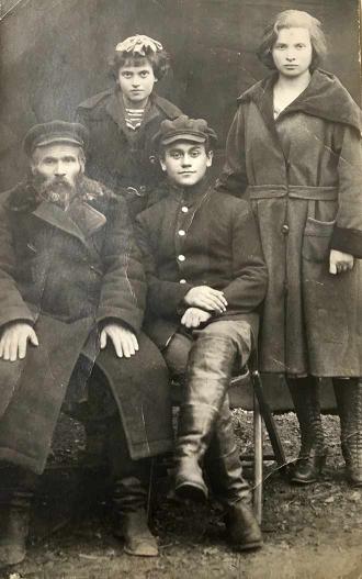 Schwarz-weiß-Gruppenfoto: Ein bärtiger Mann und ein junge sitzend, ein jüngeres und ein älteres Mädchen dahinter stehend, alle in Mänteln