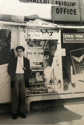 Black-and-white photograph of a man in front of a shop window display with musical instruments and Hebrew writing