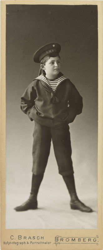 Black-and-white photograph: boy in a sailor costume standing with legs apart and arms akimbo; studio portrait