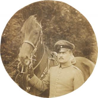 Schwarz-weiß-Foto: Uniformierter Soldat mit einem Pferd