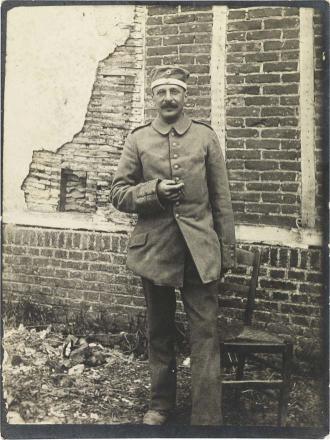 Schwarz-weiß-Foto: Ein Soldat in Uniform, rauchend, vor einem Gebäude mit bröckelndem Verputz