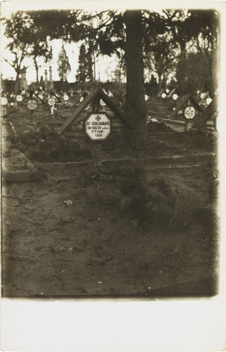 Black-and-white photograph: gravestone with cross and inscription; more graves in the background