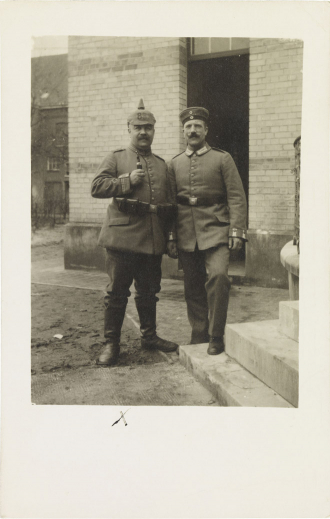 Black-and-white photograph: two soldiers in uniform, one in a spiked helmet and the other in a military cap, outside a buildi