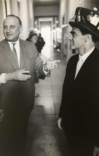 Black-and-white photo of a younger man with a decorated top hat and an older man pointing at him
