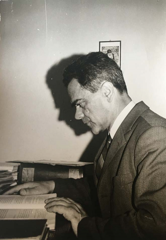 Black-and-white photograph of a man reading a book at a desk