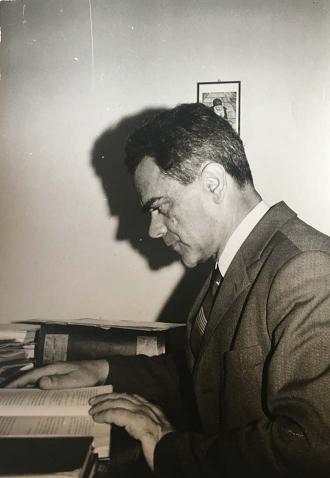 Schwarz-weiß-Foto eines Mannes, der am Schreibtisch sitzt und in einem Buch liest
