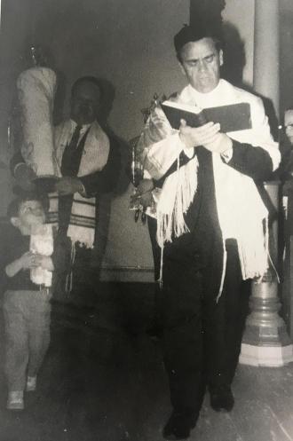 Schwarz-weiß-Foto eines stehenden Mannes mit Tallit und aufgeschlagenem Buch in den Händen