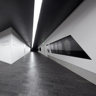 Two corridors with dark slate floors and white walls with embedded showcases.