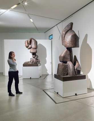 A female visitor holds a device to her ear and looks at two sculptures by Otto Freundlich