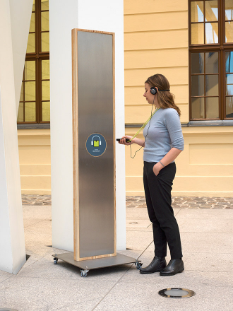 A woman holds an audio guide device to a sensor on a mobile signpost in the glass courtyard f des Jüdischen Museums Berlin
