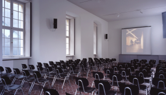 Rows of empty black chairs face the front of the room where a projector screen is located