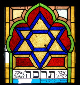 Colorfult stained glass window depicting the star of david with Hebrew text at the bottom