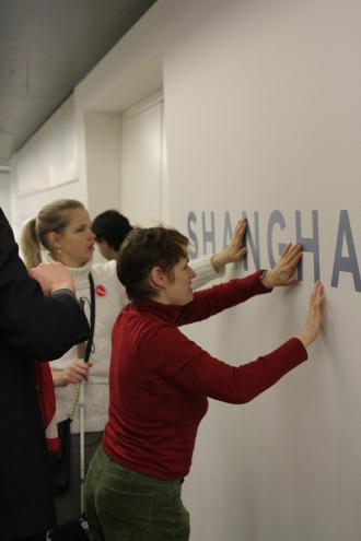 Hände erfühlen einen Schriftzug an einer Wand