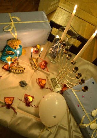 Chanukkia auf einem Tisch mit Geschenken, Luftballon und Teddybär