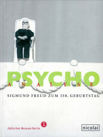 "Catalogue Cover for the the Exhibition ""PSYCHOanalyse"": a small cloth figurine of a sitting man with a white beard and glasses"
