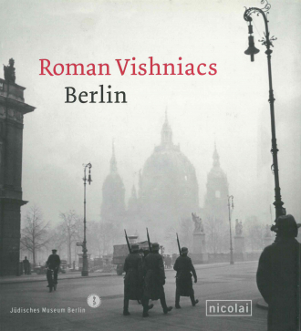 "Catalogue Cover for the Exhibition ""Roman Vishniacs Berlin"": historical black and white photograph of a small group of troops wearing large coats marching on a foggy day"