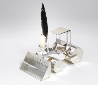Farbfotografie einer realistisch gestalteten Miniatur-Dampfwalze mit Walzrolle, Baggerschaufel und Führerhäuschen. Auf der Oberseite des stilisierten Motorraums sind ein Metallröhrchen zum Einstecken einer Feder sowie ein Kerzenhalter angebracht.