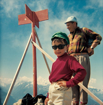A child and an adult stand near a cross on a mountaintop.